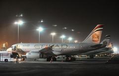 Самолеты Etihad Airways в аэропорту Абу-Даби 19 сентября 2012 года. Государственная авиакомпания ОАЭ Etihad Airways достигла принципиальной договоренности о покупке 49 процентов убыточного итальянского авиаперевозчика Alitalia, сообщила Etihad в среду. REUTERS/Ben Job
