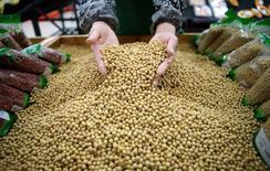 Un empleado toma en sus manos una pila de granos de soja en un supermercado en Wuhan, 14 de abril de 2014. Más banqueros chinos creen que la economía del país se ha enfriado en el segundo trimestre que a principios de año y la demanda de préstamos se ha debilitado, según reveló una encuesta del banco central publicada el miércoles. REUTERS/Stringer