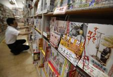 "A Japanese Manga ""Ichi Efu"" (2nd R), which centres on workers at the Fukushima Daiichi nuclear plant, is seen on a bookshelf as a staff adjusts manga comics at a bookstore in Tokyo June 23, 2014. REUTERS/Yuya Shino"