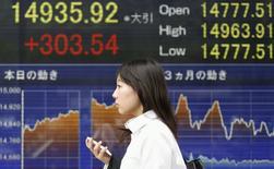 Una mujer sostiene su celular mientras camina frente a una pantalla electrónica que muestra el Nikkei japonés en Tokio, 2 de junio de 2014. El índice Nikkei de la bolsa de Tokio subió marginalmente el jueves, alejándose desde un mínimo en una semana luego de que unos datos débiles de crecimiento en de Estados Unidos apoyaron la opinión de de que la Reserva Federal de Estados Unidos mantendrá las tasas de interés bajas por más tiempo. REUTERS/Yuya Shino