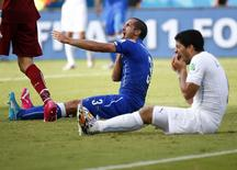 Uruguay's Luis Suarez (R) reacts after clashing with Italy's Giorgio Chiellini June 24, 2014. The Italians were still complaining about the incident when Uruguay captain Diego Godin scored with an 81st-minute header to secure a 1-0 win that sent them into the second round and eliminated Italy. REUTERS/Tony Gentile