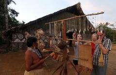 Tourists look at crafts made by members of the Amazonian Tatuyo tribe in their village June 23, 2014. REUTERS/Andres Stapff