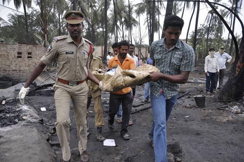 People carry the body of a victim near the site of a blast and fire at a gas pipeline at Godavari district, in Andhra Pradesh June 27, 2014. REUTERS/Stringer