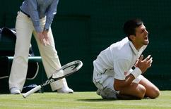 Novak Djokovic from Serbia falls during his men's singles match against Gilles Simon from France at the Wimbledon Tennis Championships, in London June 27, 2014.           REUTERS/Stefan Wermuth