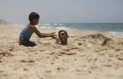 A Palestinian boy buries his brother with sand as they play on a beach in the central Gaza Strip June 26, 2014.   REUTERS/Mohammed Salem