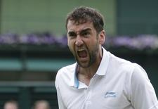 Marin Cilic of Croatia reacts after defeating Jeremy Chardy of France in their men's singles tennis match at the Wimbledon Tennis Championships, in London June 30, 2014.      REUTERS/Max Rossi