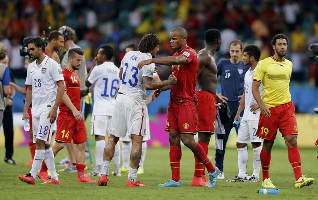 Belgium's Vincent Kompany (C, red) shakes hands with Jermaine Jones of the U.S. after their 2014 World Cup round of 16 game at the Fonte Nova arena in Salvador July 1, 2014. REUTERS/Marcos Brindicci