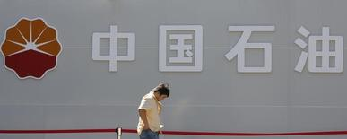 Мужчина проходит мимо логотипа PetroChina на заправке в Пекине 29 августа 2013 года. Французская нефтяная компания Total ведет переговоры с PetroChina о продаже ей доли в одном из китайских НПЗ, которой Total владела почти 20 лет. REUTERS/Kim Kyung-Hoon