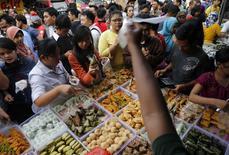 Gente compra comida en un mercado durante el mes sagrado de Muslim, en Ramadan en Jakarta, 30 de junio de 2014. Las bolsas de Asia cotizaban el jueves cerca de unos máximos en tres años en momentos en que los inversores esperan el reporte de las nóminas de empleo no agrícola en Estados Unidos para ver si la economía de ese país está ganando impulso.   REUTERS/Beawiharta
