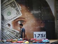 Пешеход проходит мимо пункта обмена валюты в Каире 29 мая 2014 года. Курс доллара близок к недельному максимуму после публикации неожиданно хороших данных о рынке занятости США. REUTERS/Amr Abdallah Dalsh