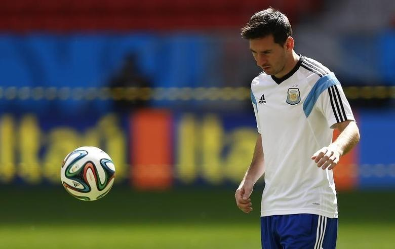 Argentina's Lionel Messi looks at the ball during a team training session at the national stadium in Brasilia July 4, 2014, one day before their 2014 World Cup quarter-final soccer match against Belgium.  REUTERS/Dominic Ebenbichler