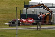 The car of Ferrari Formula One driver Kimi Raikkonen of Finland is lifted off the track following a crash during the British F1 Grand Prix at the Silverstone Race circuit, central England July 6, 2014.  REUTERS/Phil Noble