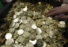Десятирублевые монеты на монетном дворе в Санкт-Петербурге, 9 февраля 2010 года. Рубль дешевеет в понедельник за счет локального спроса на валюту в условиях сохранения напряженной ситуации на востоке Украины и на фоне проходящих летом дивидендных выплат. REUTERS/Alexander Demianchuk