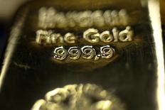 Слиток золота в хранилище Pro Aurum в Мюнхене, 3 марта 2014 года. Цены на золото снижаются за счет подъема на фондовых рынках и вероятности более раннего начала повышения процентных ставок ФРС в связи с сильным показателем занятости в США. REUTERS/Michael Dalder