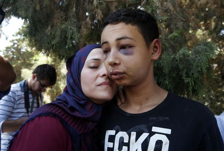 Tariq Khdeir (R) is greeted by his mother after being released from jail in Jerusalem July 6, 2014. An Israeli judge on Sunday released from jail and placed under house arrest the 15-year-old American of Palestinian descent whose apparent beating by Israeli police in East Jerusalem has drawn U.S. concern. Tariq Khdeir from Tampa, Florida, is a cousin of Mohammed Abu Khudeir, 16, whose abduction and killing in Jerusalem on Wednesday sparked violent protests and calls from Palestinians for a new uprising against Israel.  REUTERS/Ronen Zvulun (JERUSALEM - Tags: POLITICS CRIME LAW CIVIL UNREST TPX IMAGES OF THE DAY)