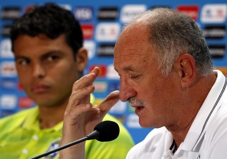Brazil's team coach Luiz Felipe Scolari (R) speaks as Thiago Silva listens during a media conference at Mineirao stadium in Belo Horizonte July 7, 2014. REUTERS/David Gray