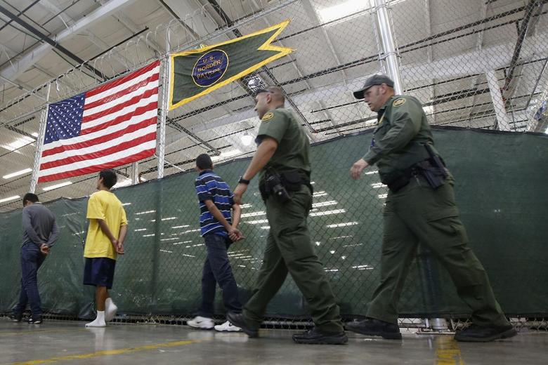 Detainees are escorted to an area to make phone calls as hundreds of mostly Central American immigrant children are being processed and held at the U.S. Customs and Border Protection (CBP) Nogales Placement Center in Nogales, Arizona, June 18, 2014.   REUTERS/Ross D. Franklin/Pool