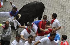 A runner gored in the leg by a Victoriano del Río fighting bull, falls at the entrance to the bullring during the third running of the bulls of the San Fermin festival in Pamplona July 9, 2014. Three runners were hospitalized following a run that lasted three minutes and twenty three seconds, according to local media. REUTERS/Eloy Alonso
