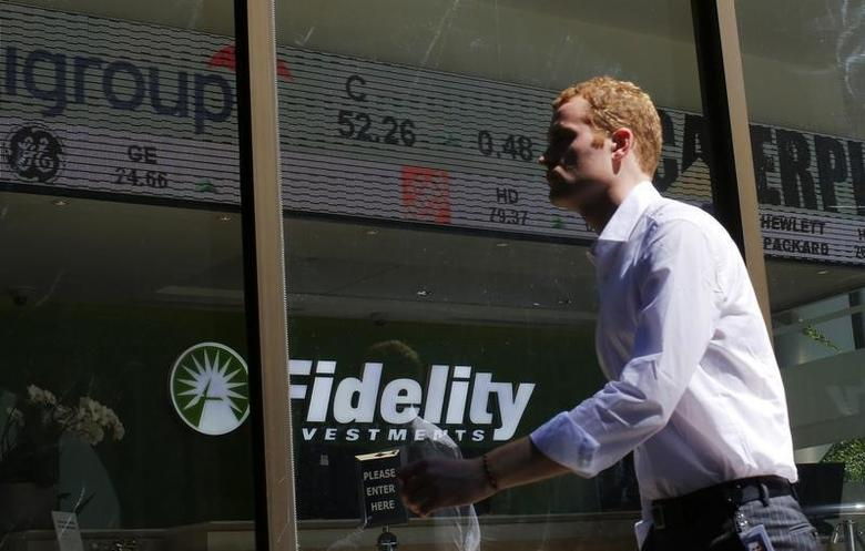 A pedestrian walks past a stock ticker at a Fidelity Investments office in Boston, Massachusetts July 31, 2013.   REUTERS/Brian Snyder