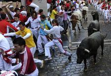 El penúltimo encierro de las fiestas de San Fermín se desarrolló el domingo sin incidencias importantes ni heridos por asta de toro en el regreso de la ganadería de Adolfo Martín a los festejos. En la imagen, corredores delante de los toros de Adolfo Martín en la esquina de Estafeta en el séptimo encierro de los sanfermines, el 13 de julio de 2014. REUTERS/Eloy Alonso