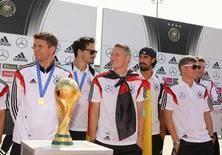German soccer players Thomas Mueller, Mats Hummels, Bastian Schweinsteiger, Sami Khedira and Toni Kroos stand behind the World Cup trophy at Tegel airport in Berlin, July 15, 2014.    REUTERS/Karina Hessland/Pool