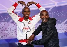 British Olympic athlete Mo Farah adjusts the clothing on one of two waxworks, one will be displayed in London and the other in Blackpool at Madame Tussauds, in London April 14, 2014. REUTERS/Olivia Harris