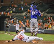 Baltimore Orioles baserunner Matt Wieters (bottom) slides in safely as Texas Rangers catcher A.J. Pierzynski reaches for the throw following Nate McLouth's run-scoring base hit in the eighth inning off Texas Rangers relief pitcher Jason Frasor  during their MLB American League baseball game in Baltimore, Maryland July 11, 2013.  REUTERS/Doug Kapustin