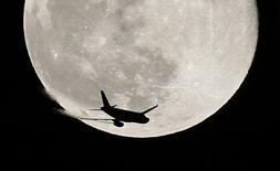 An airplane is silhouetted against a full moon in the sky over London January 1, 2010. REUTERS/Suzanne Plunkett