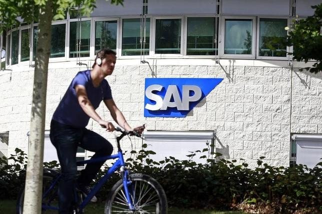 A man cycles past the SAP logo at its offices in the CityWest complex, Dublin September 5, 2013. Picture taken September 5, 2013. REUTERS/Cathal McNaughton