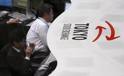 Участники торгов на Токийской фондовой бирже 30 декабря 2013 года. Азиатские фондовые рынки, кроме Южной Кореи, снизились в четверг под влиянием отдельных отраслей и локальных новостей. REUTERS/Yuya Shino