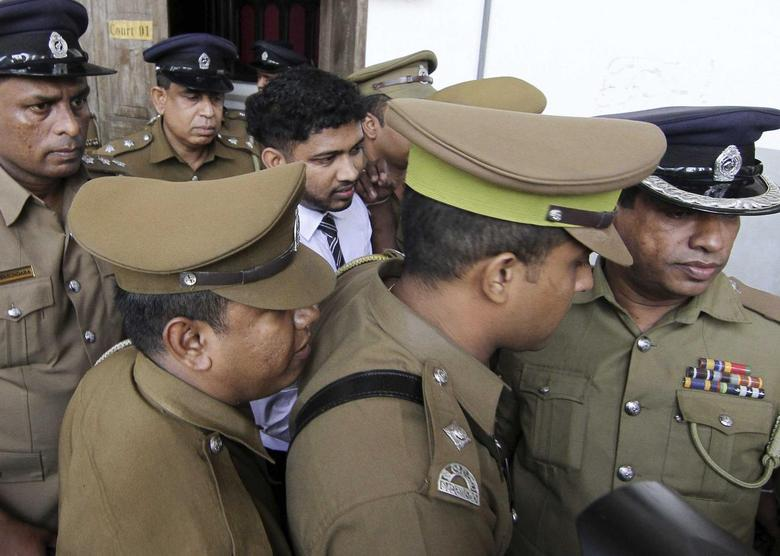 Sampath Vidanapathirana (in white), Sri Lanka's ruling party politician, is led away from the High Court by police officers in Colombo July 18, 2014.   REUTERS/Stringer