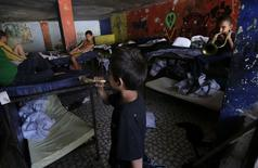 "Children play trumpets in a room inside a home known as ""La Gran Familia"" (The Big Family), in the western city of Zamora July 17, 2014. REUTERS/Henry Romero"