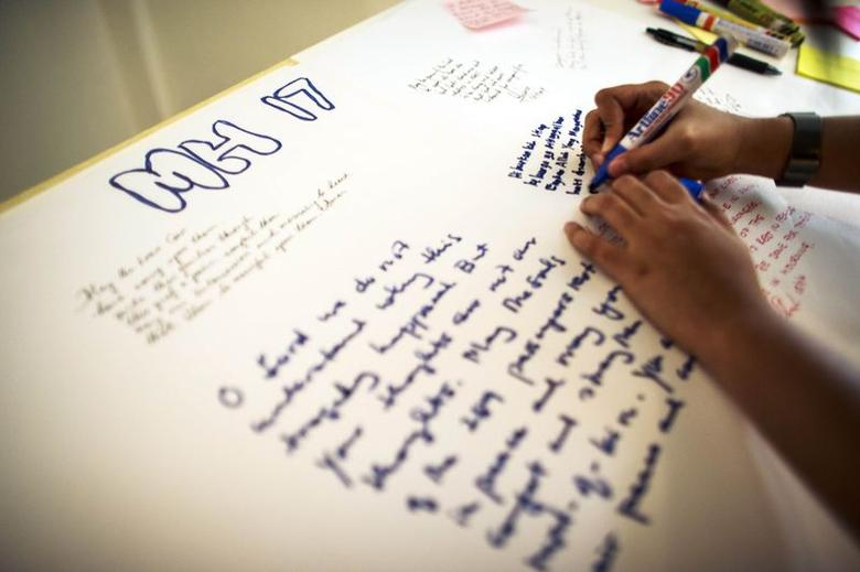 A woman writes messages during a special prayer for the victims of downed Malaysia Airlines Flight MH17 in Kuala Lumpur July 18, 2014. REUTERS/Athit Perawongmetha