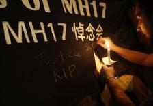 Memorial improvisé en Indonésie, à Kuala Lumpur. La compagnie aérienne Malaysia Airlines annonce qu'elle versera une indemnité de 5.000 dollars à chaque famille de passagers morts dans le crash du vol MH17 Amsterdam-Kuala Lumpur jeudi dernier dans l'est de l'Ukraine. /Photo prise le 20 juillet 2014/REUTERS/Edgar Su