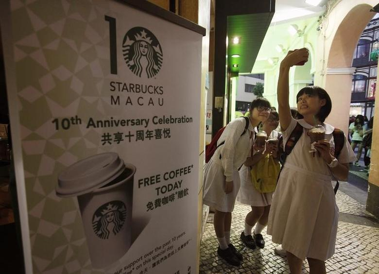Schoolgirls take a group photo in front of a Starbucks outlet in Macau October 10, 2012. REUTERS/Bobby Yip/Files