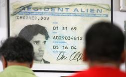 Workers queue for lunch in front of a poster-size photo of the first alien resident card of former company Chief Executive Dov Charney at the American Apparel factory in downtown Los Angeles, in this October 17, 2008 file photo. REUTERS/Lucy Nicholson/Files