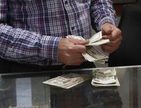 Мужчина пересчитывает доллары в пункте обмена валюты в Триполи 30 марта 2014 года. Курс доллара к корзине основных валют близок к шестинедельному пику на торгах в Азии, а евро снизился до минимальной с начала года отметки из-за расхождения в прогнозах процентных ставок для США и еврозоны. REUTERS/Ismail Zitouny