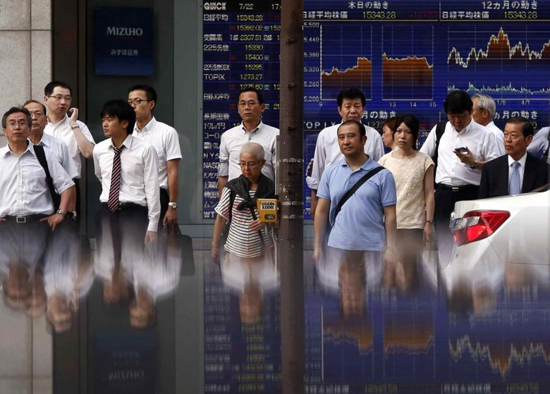 Pedestrians standing in front of an electronic board showing the graph of recent fluctuations in Japan's Nikkei average outside a brokerage are reflected in a polished stone surface, in Tokyo July 22, 2014. REUTERS/Yuya Shino