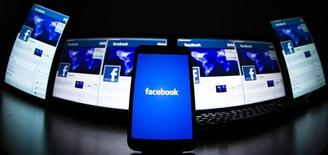Логотип Facebook на экране мобильного телефона в Лавиньи 16 мая 2012 года. Крупнейшая в мире социальная сеть Facebook Inc увеличила выручку во втором квартале на 61 процент за счет быстрых темпов роста мобильной рекламы, превзойдя прогнозы Уолл-стрит и подтолкнув к рекордной отметке свои акции. REUTERS/Valentin Flauraud