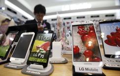 Продавец пользуется мобильным телефоном в магазине в Сеуле 22 июля 2014 года. Корейская LG Electronics Inc отчиталась о лучшей квартальной прибыли за более чем три года, превысившей прогнозы аналитиков благодаря продажам телевизоров и успехам подразделения мобильных телефонов. REUTERS/Kim Hong-Ji