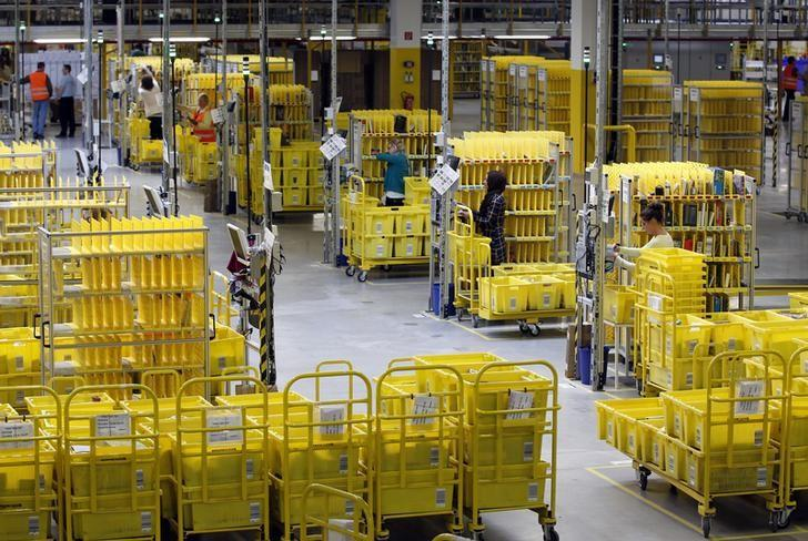 Workers collect items at Amazon's logistics centre in Graben near Augsburg December 16, 2013. REUTERS/Michaela Rehle/Files