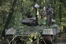 A pro-Russian separatist from the Vostok (East) battalion poses for a picture atop a T-64 tank in Donetsk, eastern Ukraine, July 16, 2014. Fighting raged in Ukraine's east on Wednesday when separatists tried to break through the lines of government forces near the border with Russia and a tentative step towards agreeing conditions for a ceasefire failed.      REUTERS/Maxim Zmeyev (UKRAINE - Tags: POLITICS CIVIL UNREST MILITARY)