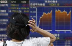Женщина у брокерской конторы в Токио 19 июня 2014 года. Азиатские фондовые рынки выросли за неделю благодаря улучшению макроэкономических показателей США, Китая и Европы. REUTERS/Yuya Shino