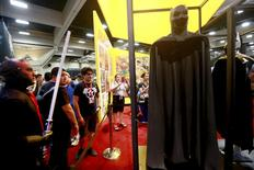 Attendees look over the new Batman outfit on at the comic franchise's 75th anniversary display during the 2014 Comic-Con International Convention in San Diego, California July 24, 2014.  REUTERS/Sandy Huffaker