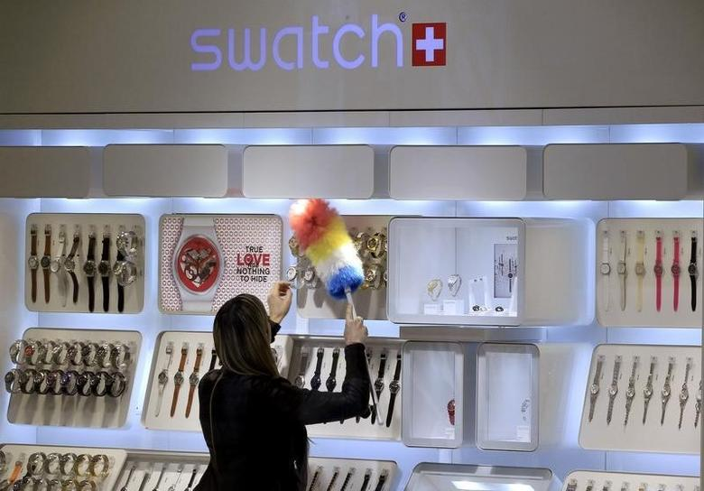 A shop assistant uses a feather duster to clean a display of Swatch watches at a department store in Zurich February 4, 2013. REUTERS/Arnd Wiegmann