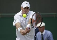 John Isner of the U.S.  hits a return to Feliciano Lopez of Spain during their men's singles tennis match at the Wimbledon Tennis Championships, in London June 30, 2014.      REUTERS/Max Rossi/Files