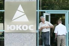 Люди у входа в главный офис Юкоса в Москве 24 июля 2003 года. Россия усомнилась в полномочиях международного арбитража в Гааге, обязавшего её выплатить $51,57 миллиарда компенсации ущерба акционерам прекратившего существование Юкоса и оспорит вердикт в судах Нидерландов, заявил Минфин. REUTERS/Viktor Korotayev