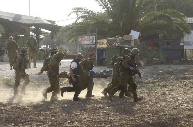 Israeli soldiers carry their comrade on a stretcher after he was wounded in a Palestinian mortar strike, as they evacuate him from the scene outside the central Gaza Strip July 28, 2014. REUTERS/Ido Erez
