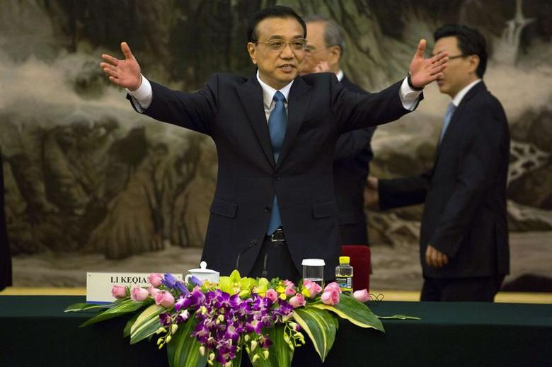 Chinese Premier Li Keqiang (front) gestures for delegates to sit before a meeting at the Great Hall of the People in Beijing July 22, 2014. REUTERS/Ng Han Guan/Pool