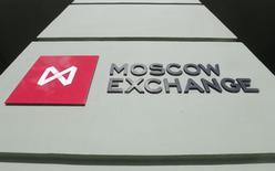 Логотип у входа в помещение Московской биржи 14 марта 2014 года. Торги акциями и облигациями на основном рынке Московской биржи были приостановлены около 16.00 МСК в среду, причины остановки изучаются, сообщила биржа. REUTERS/Maxim Shemetov